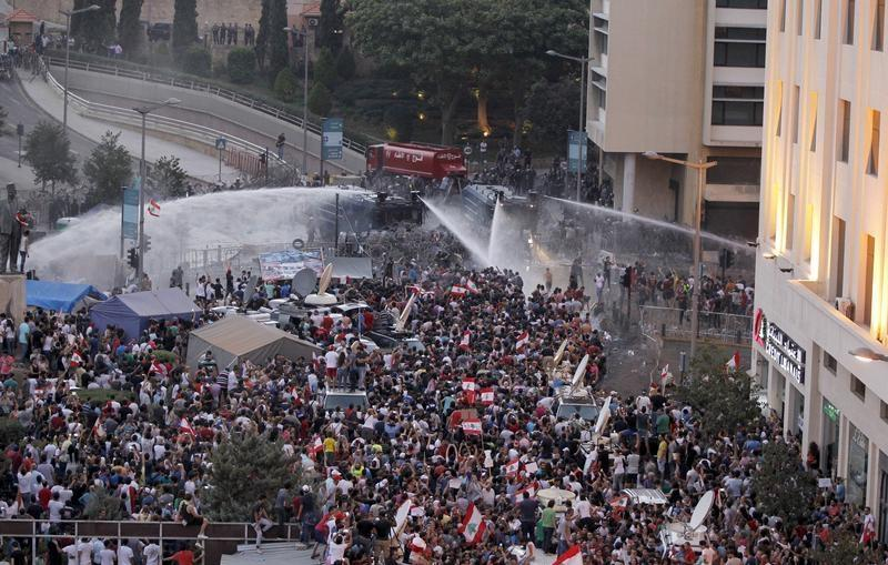 Lebanese protesters are sprayed with water during a protest against corruption and against the government's failure to resolve a crisis over rubbish disposal, near the government palace in Beirut, Lebanon August 23, 2015. Lebanese security forces fired water cannon at protesters demonstrating against the government near Prime Minister Tammam Salam's offices in Beirut on Sunday, live television pictures showed. REUTERS/Mohamed Azakir - RTX1PC2G